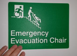 Emergency Evacuation Chair sign, in green, with Braille and Tactile characters, and accessible means of egress icon wheelchair symbol