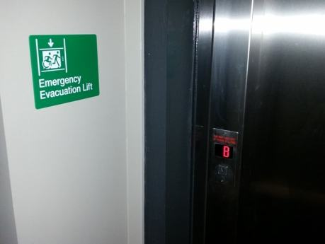 Emergency Evacuation Lift sign on a wall next to the lift doors, in green, with Braille and Tactile characters, and accessible means of egress icon wheelchair symbol-min.jpg