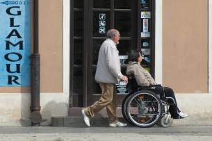 A gentlemen pushing a lady in a wheelchair past a shop that has two steps and a sign in the window saying NO DOGS