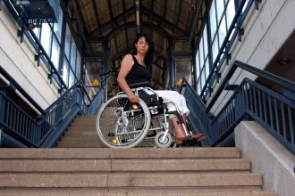 A lady in a wheelchair stares down from the top of the stairs